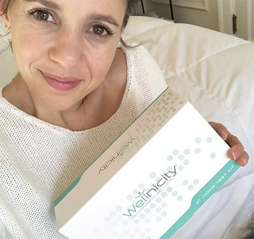 photo of Sarah holding Wellnicity test kit